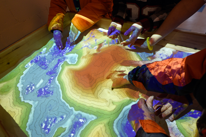 Children play with an augmented reality sandbox which uses computer software and a projector that displays cartographic features in real time as the sand's surface is changed during STEAM Night, which celebrated the 50th anniversary of the Needham Science Center at Newman Elementary School on Thursday, Mar. 19, 2015. (Wicked Local Staff Photo / Brett Crawford)