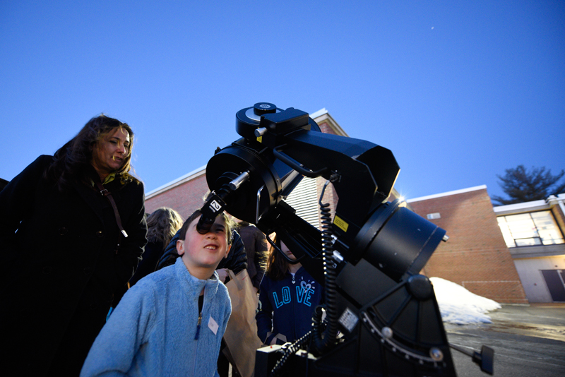 Nathaniel Coutu, 6, of Needham looks through a telescope to view the planet Jupiter and four of its moons as his mother Clary stands by during STEAM Night, which celebrated the 50th anniversary of the Needham Science Center at Newman Elementary School on Thursday, Mar. 19, 2015. (Wicked Local Staff Photo / Brett Crawford)