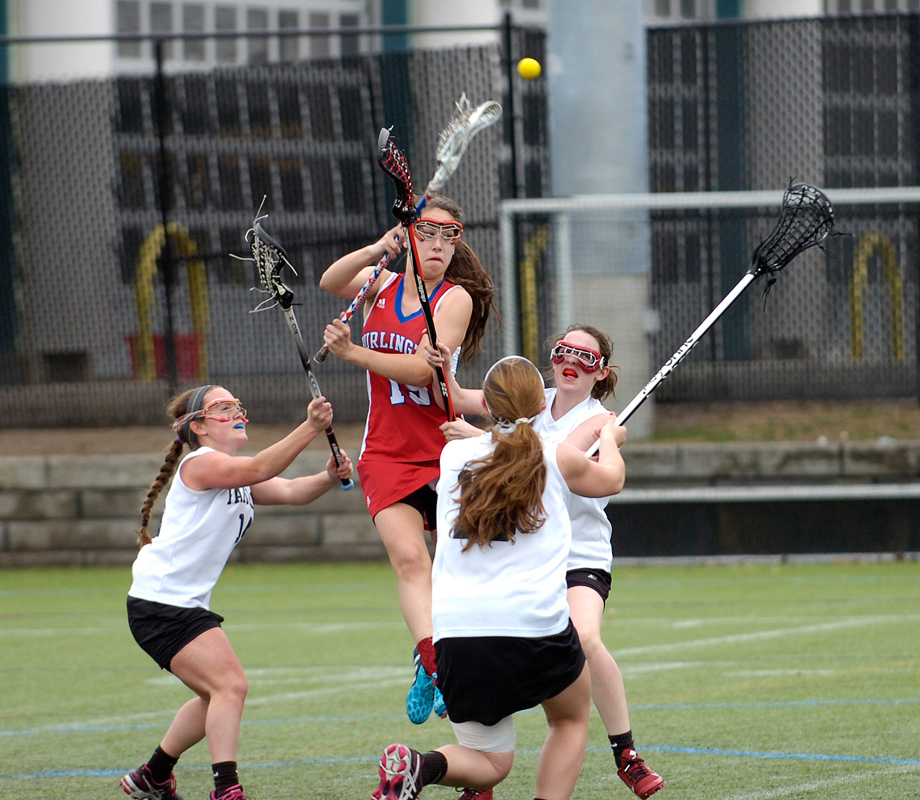 Burlington's Emily Moreira fires a shot for a goal while surrounded by Watertown's defense on Friday, Apr. 17, 2015. (Wicked Local Staff Photo / Brett Crawford)