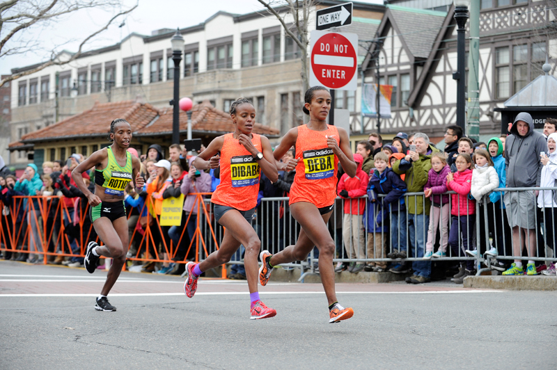 Caroline Rotich of Kenya (left) chases Mare Dibaba of Ethiopia (center) and Buzunesh Deba of Ethiopia during the 119th Boston Marathon on Monday, Apr. 20, 2015. Rotich finished 1st with a time of 2:24:55, followed by Dibaba with a time of 2:24:59, and Deba with a time of 2:25:09. (Wicked Local Staff Photo / Brett Crawford)
