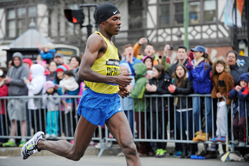 Lelisa Desisa of Ethiopia runs down Beacon St. through Coolidge Corner in Brookline during the 119th Boston Marathon on Monday, Apr. 20, 2015. Desisa placed 1st with a finish time of 2:09:17. (Wicked Local Staff Photo / Brett Crawford)