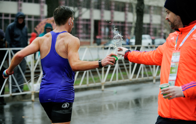 A runner takes a cup of Gatorade from a volunteer on Beacon St. in Brookline during the 119th Boston Marathon on Monday, Apr. 20, 2015.  (Wicked Local Staff Photo / Brett Crawford)