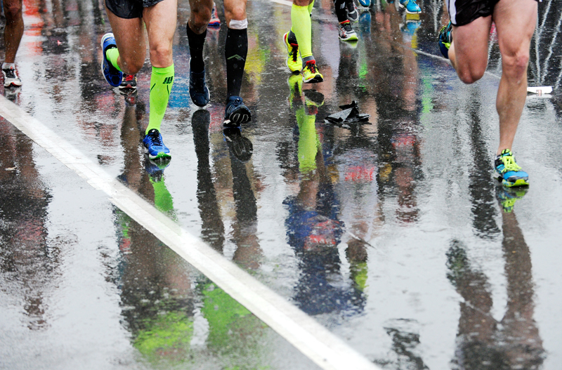 Runners are reflected on a rain-soaked Beacon St. in Brookline during the 119th Boston Marathon on Monday, Apr. 20, 2015. (Wicked Local Staff Photo / Brett Crawford)