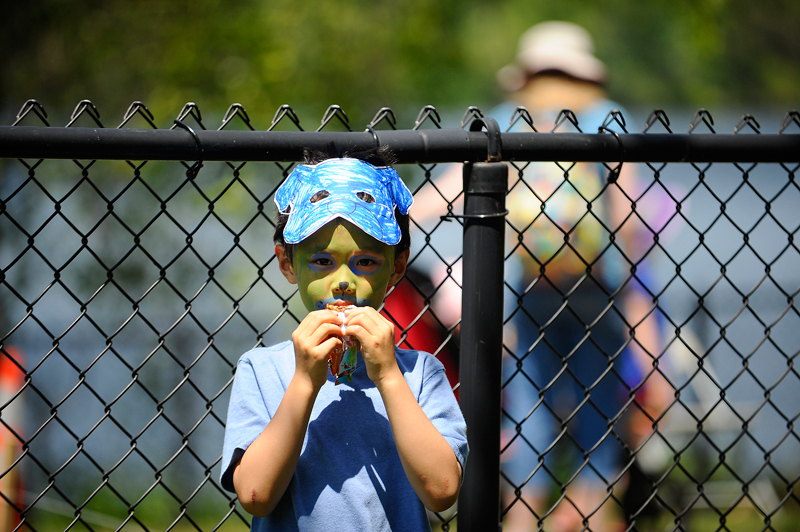 Jack Wang, 6, of Cambridge enjoys a snack while wearing a mask he made on his head and after getting his face painted during Fresh Pond Day in Cambridge on Saturday, May 30, 2015. (Wicked Local Staff Photo / Brett Crawford)
