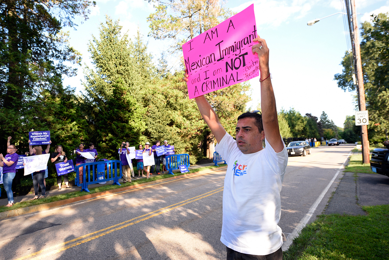 Victor Arellano of Everett, who is Mexican, holds up a sign during a protest against Donald Trump.(Wicked Local Staff Photo/Brett Crawford)