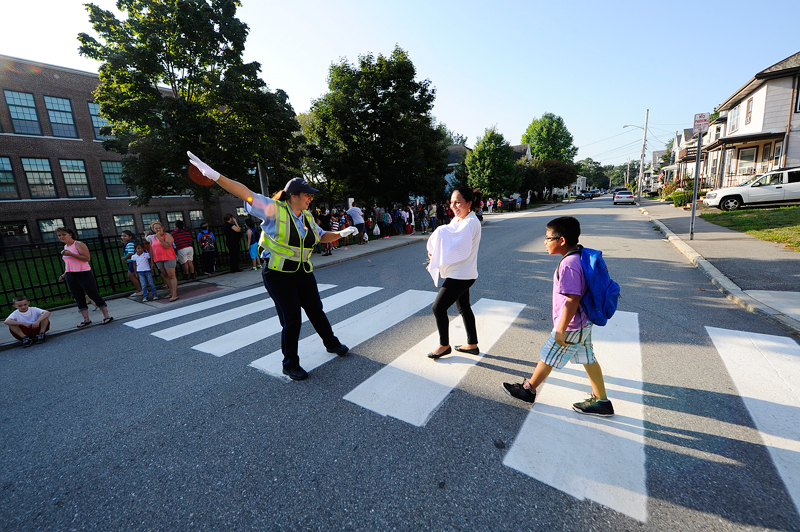 Traffic Supervisor Nicole Spoto helps Silvia Cabrera and her 5th-grader son Junior Cabrera, 10, across the street on the first day of school at Whittemore Elementary School in Waltham on Tuesday, Sep. 1, 2015. (Wicked Local Staff Photo/Brett Crawford)