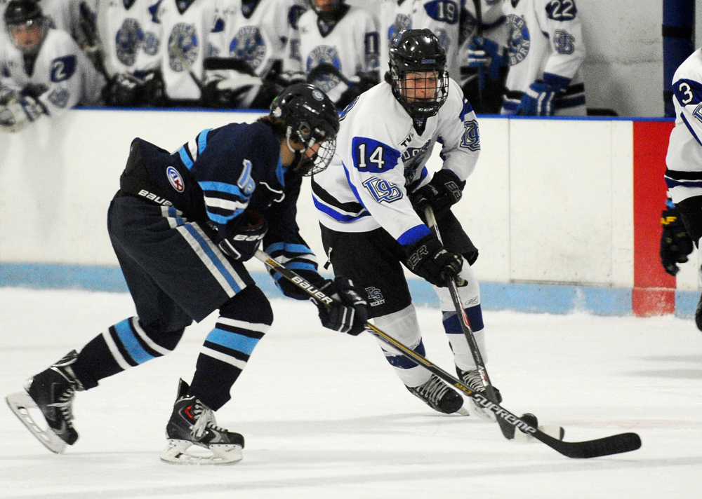 Dover-Sherborn's Cole Condon (right) skates with the puck while defended by Medfield's Sean Tyer on Wednesday, Dec. 23, 2015.