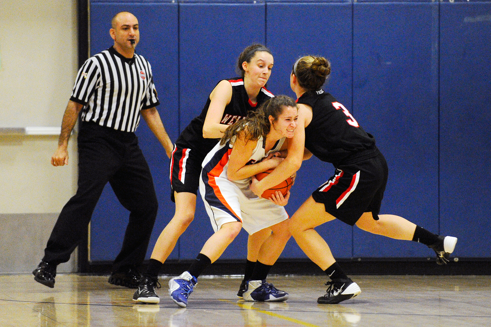 Walpole's Melanie Weber holds onto the ball as Wellesley's Katie Williamson (left) and Emma Ivey fight for possession during a game on Tuesday, Dec. 22, 2015.