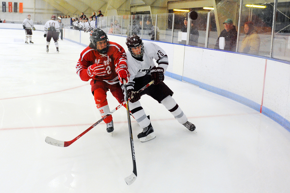 North Attleboro's Vincent Zammiello and Dedham's Brendan St. Clair battle for the puck as it goes airborn on Wednesday, Dec. 30, 2015.