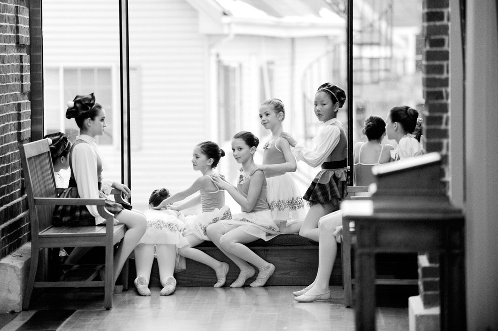 Members of the Charles River Ballet Academy give each other back massages while waiting for their turn to perform at Needham Town Hall during the annual New Year's Needham event on Thursday, Dec. 31, 2015.