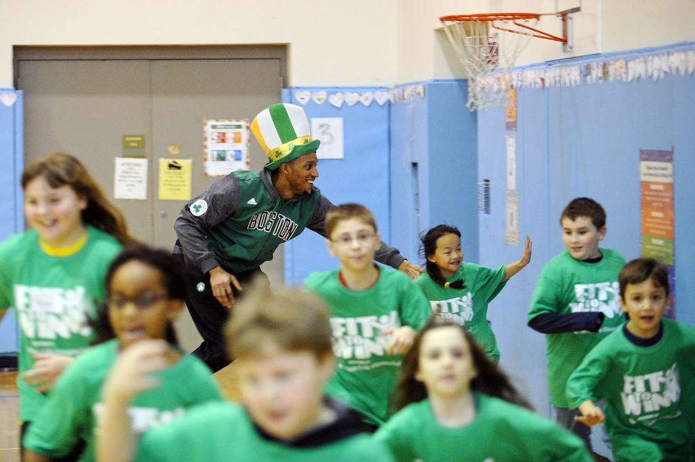 Boston Celtics player Evan Turner tags children as they run around the gym at the St. Patrick's Day themed conclusion of Fit to Win with the Boston Celtics, sponsored by Sun Life, at Northeast Elementary School in Waltham on Thursday, Mar. 10, 2016.