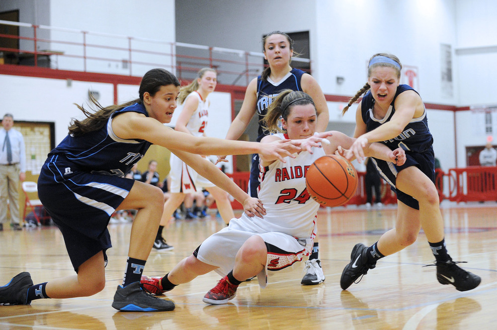 Watertown's Nicole Lanzo (center) dives to gain possession of a loose ball with Triton's Tessa Lafrance (left) and Morgan Snow during a sectional semifinal at Wakefield Memorial High School on Wednesday, Mar. 9, 2016. Watertown defeated Triton 43-29.