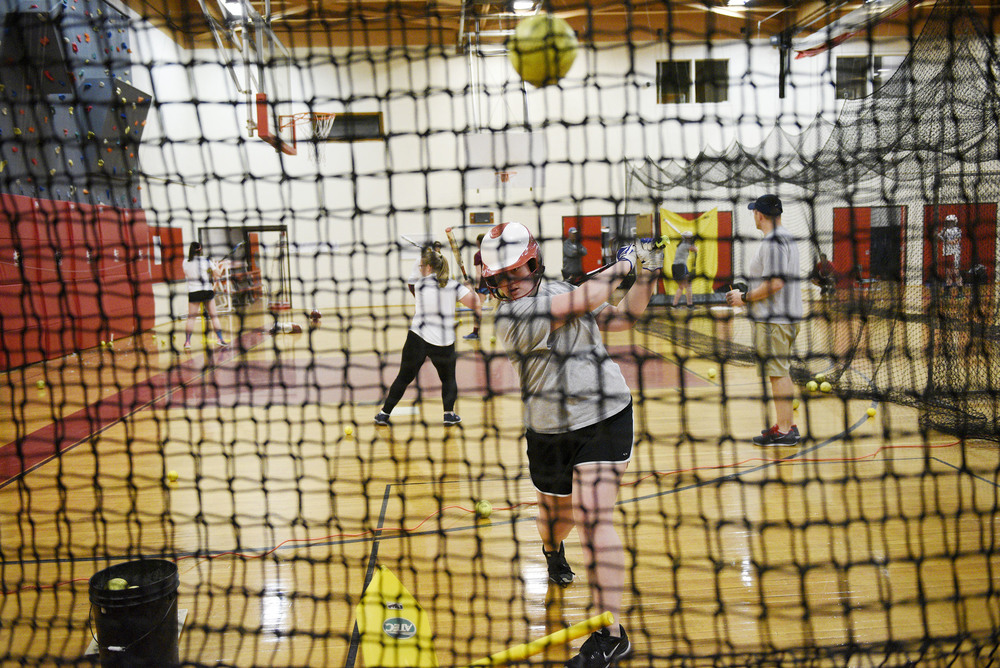 Waltham High School sophomore Cara Ferguson, 15, practices hitting balls of a tee into a net during girls varsity softball practice on Monday, Mar. 28, 2016.