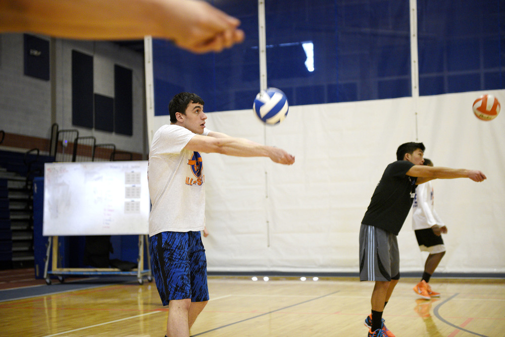 Newton South High School varsity captain Eli Braginsky bumps the ball during spring volleyball tryouts on Monday, Mar. 21, 2016.