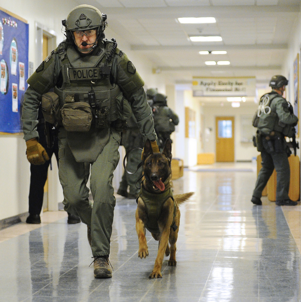 "A NEMLEC K9 police officer and his dog move through a hallway during the training drill simulating an ""active shooter on campus"" scenario at the Middlesex Community College Bedford campus on Friday, Mar. 18, 2016."
