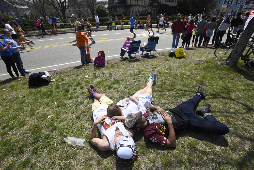 Spectators relax on a grassy section in Newton during the 120th running of the Boston Marathon on Monday, April 18, 2016.