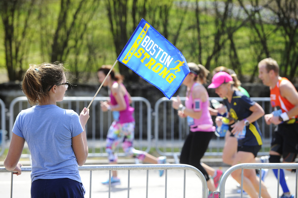 Maya Benway, 12, of Acton holds a Boston Strong flag as runners make their way up Heartbreak Hill in Newton during the 120th running of the Boston Marathon on Monday, April 18, 2016.