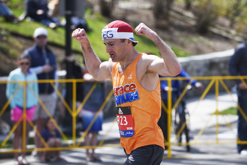 Gregory Picklesimer of team Somerville Road Runners pumps up himself and the crowd as he makes his way up Heartbreak Hill in Newton during the 120th running of the Boston Marathon on Monday, April 18, 2016.