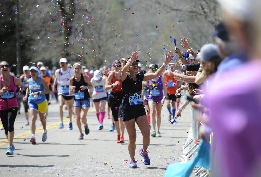 Confetti gets thrown as Muriel Salimin of New York runs by her supporters near the top of Heartbreak Hill in Newton during the 120th running of the Boston Marathon on Monday, April 18, 2016.