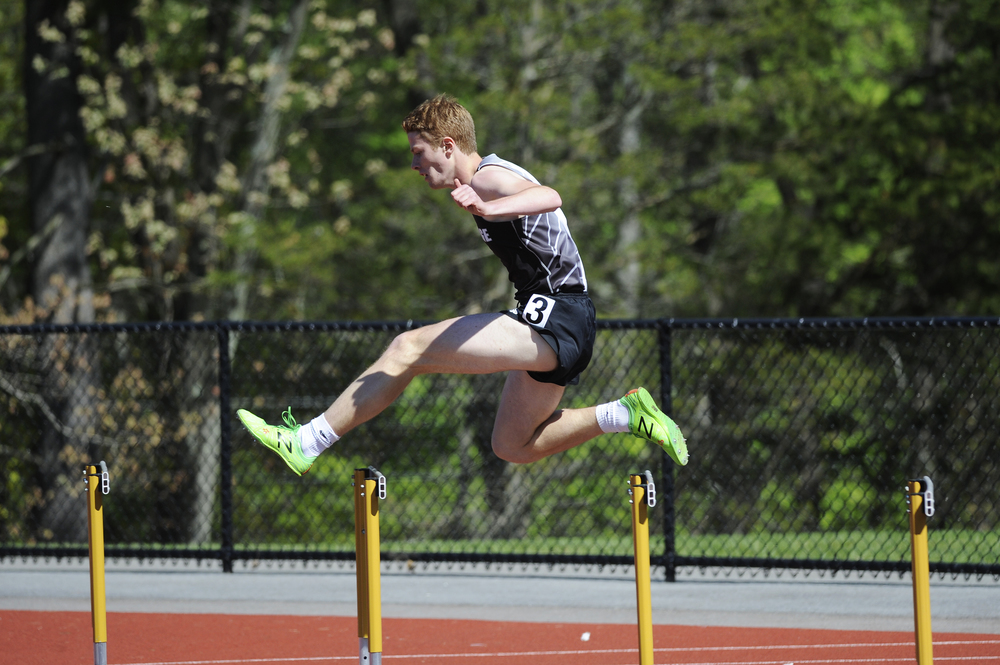 Cambridge High School's Will MacArthur competes in the 400m hurdles to place 1st in his heat at the Dual County League's track and field championship at Regis College in Weston on May 18, 2016.