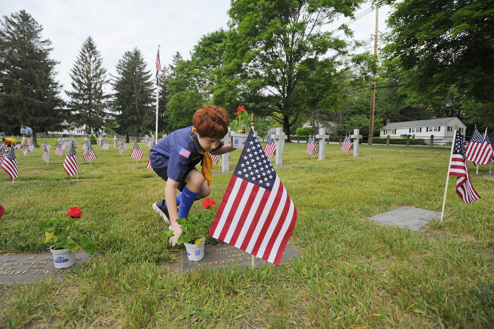 A Cub Scout Pack 136 member places flowers by veterans' graves in Wildwood Cemetery in Wilmington on May 28, 2016.