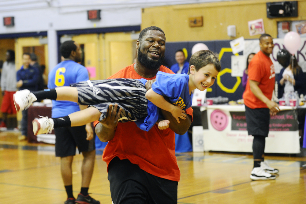 New England Patriots guard Jonathan Cooper lifts Ethan Kapcowitz, 8, while having fun at the Needham High School Boosters Celebrity Basketball game on May 5, 2016.