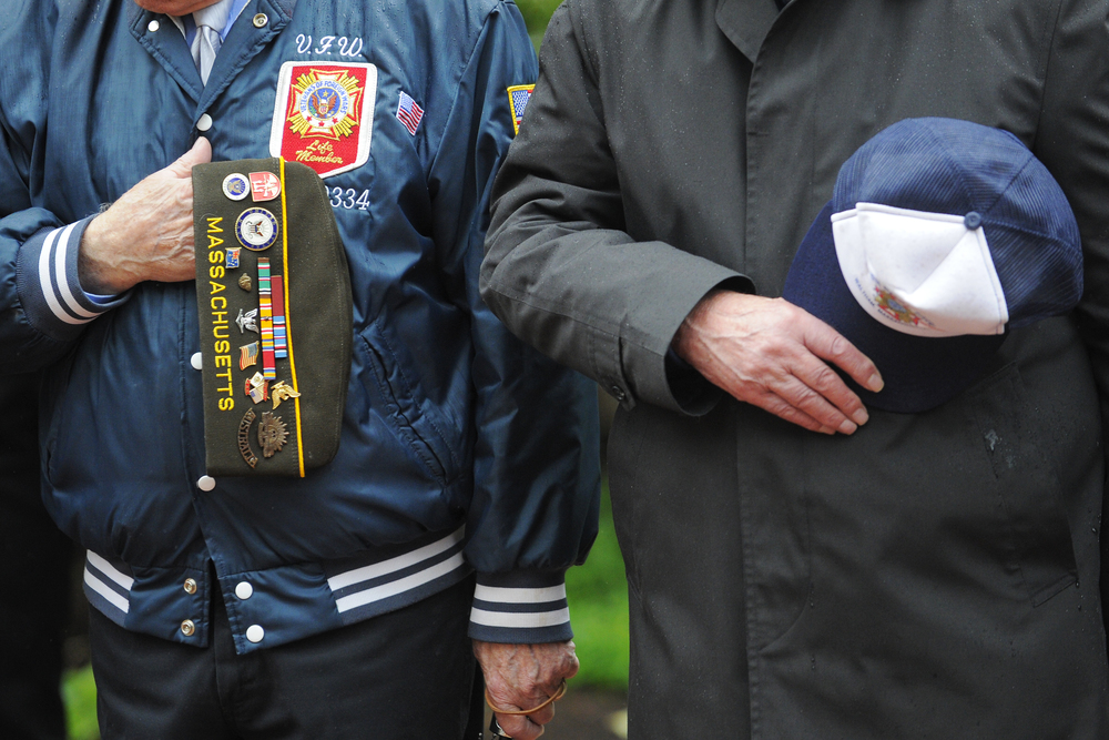 Veterans hold their caps during a prayer at Waltham's Memorial Day service at the Circle of Remembrance on the town common on May 30, 2016.