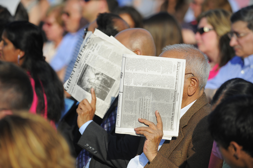 Attendees shade themselves from the sun with newspapers during Westford Academy's graduation on Friday, June 3, 2016.
