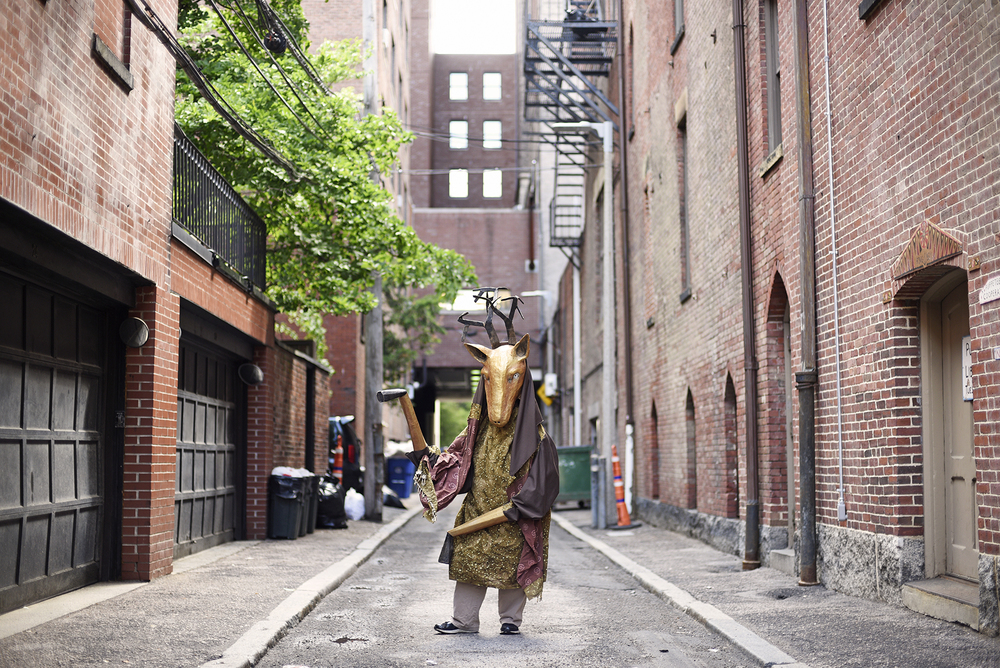 Puppeteer Sara Peattie (dressed in a wearable deer puppet she designed) stands in public alley #437 in Boston where her studio and The Puppet Free Library (which gives out puppets for people to borrow for free) are located on Monday, June 6, 2016.