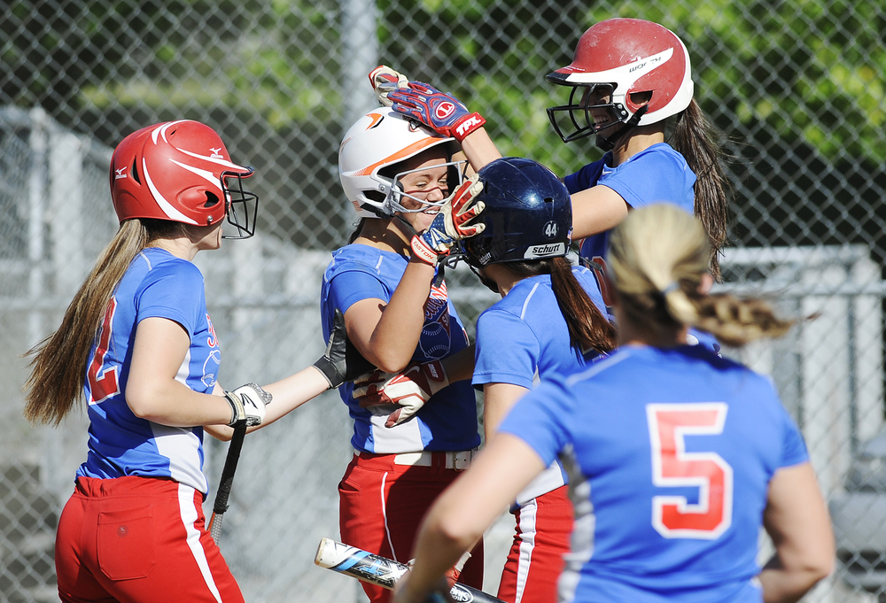 Teammates surround Tewksbury's Kayla Von Kahle (wearing white helmet) at home plate after she ran in the game-tying run during the Div. 2 state semifinal game against Burlington at Martin Field in Lowell on Friday, June 10, 2016. Tewksbury won 3-2.