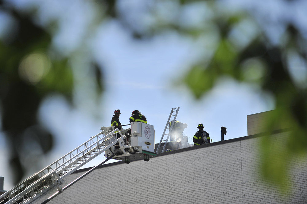 Firefighters open up the roof while battling a two-alarm blaze on the roof of Random Hall, a MIT dormitory, on Massachusetts Avenue on Tuesday, June 21, 2016.