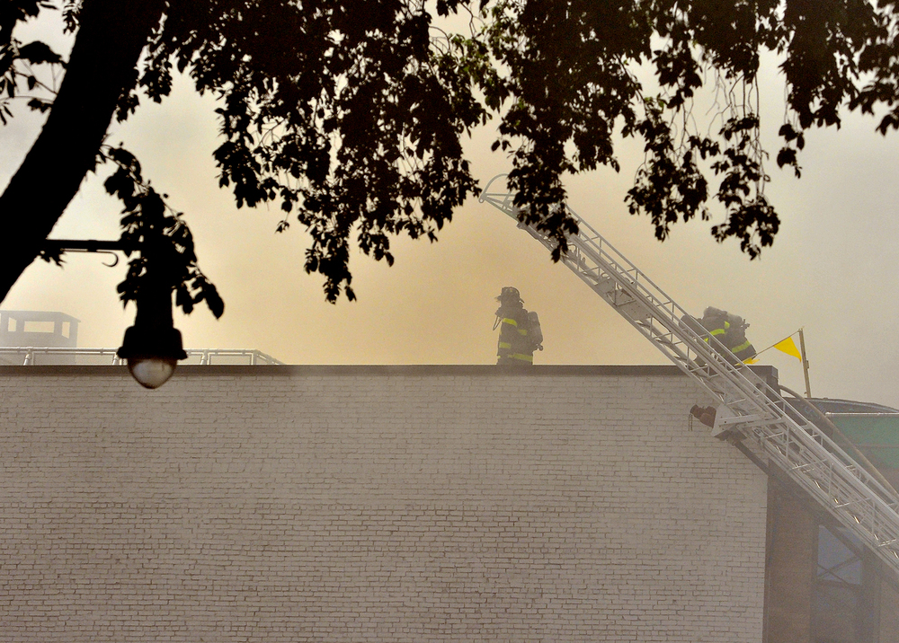 Firefighters make their way onto the roof to battle a two-alarm blaze on the roof of Random Hall, a MIT dormitory, on Massachusetts Avenue in Cambridge on Tuesday, June 21, 2016.