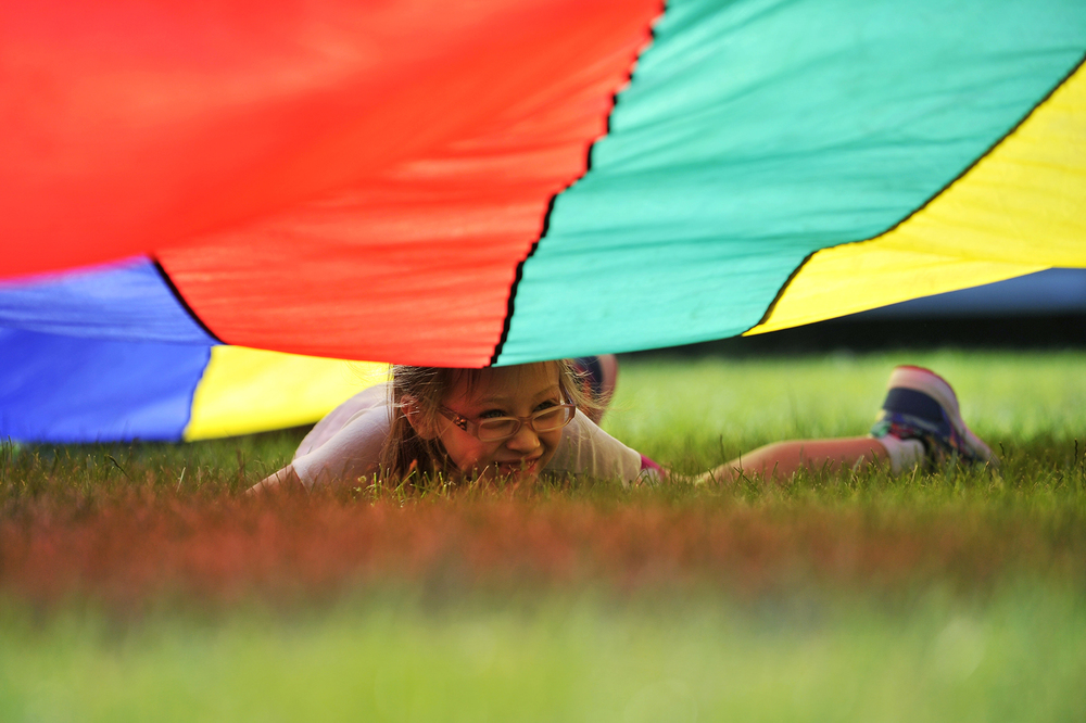 "Sophie Ledoux, 8, of Billerica crawls under a parachute during a game of ""cat and mouse"" on the first day of the Superstars camp at Vining Elementary School in Billerica on Monday, June 27, 2016."