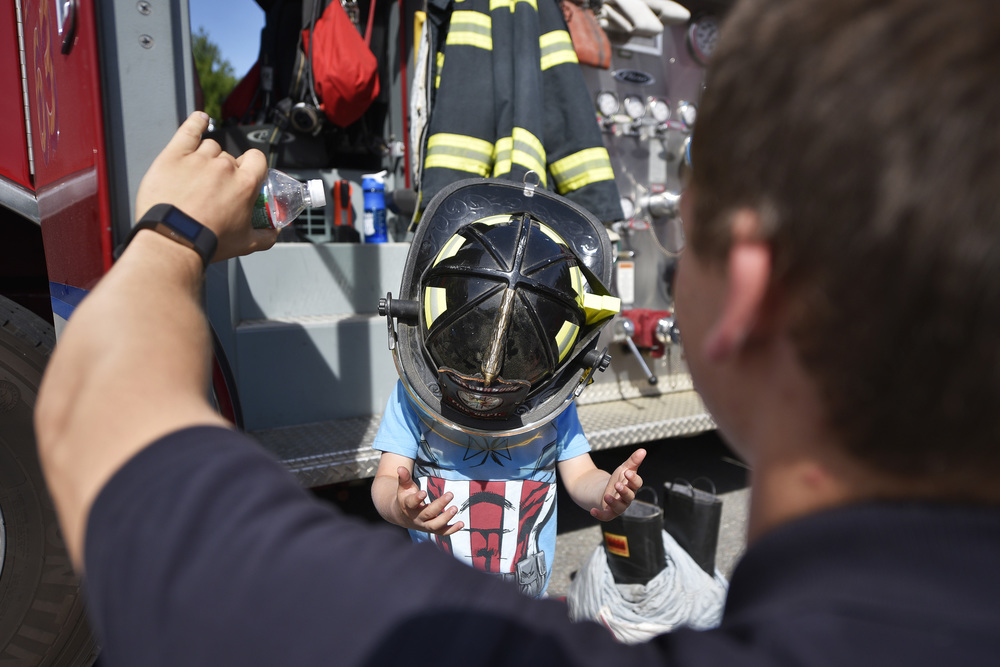 A firefighter helmet falls over the face of a young boy who tries it on for size at the 15th annual Emergency Vehicle Day at Sargent Memorial Library in Boxborough on Tuesday, July 12, 2016.