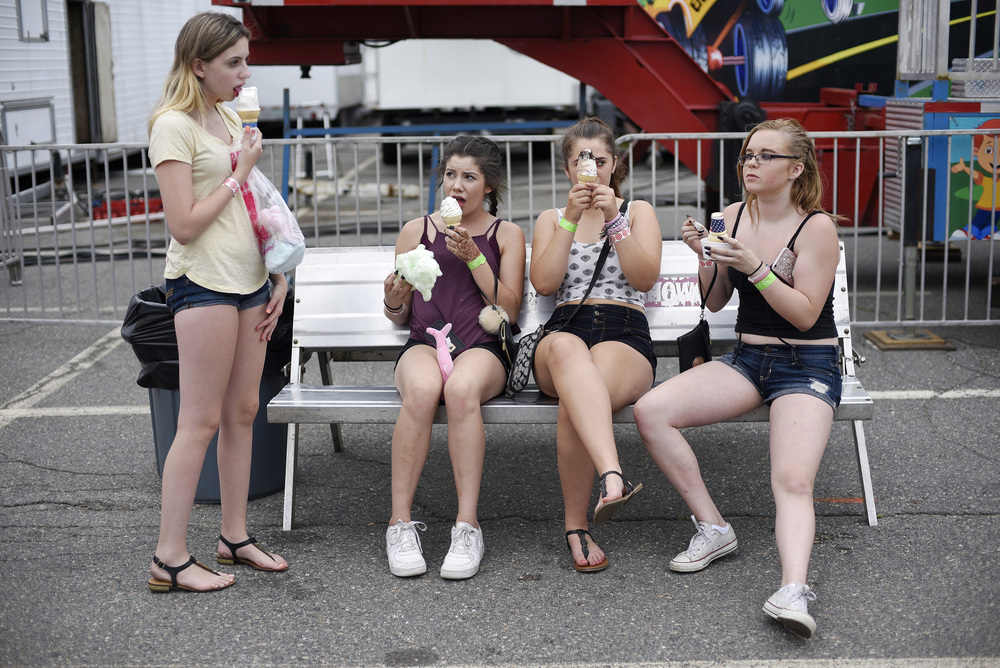 Teens eat ice-cream during the carnival at Wilmington's 36th annual July 4th celebration on Friday, July 1, 2016.