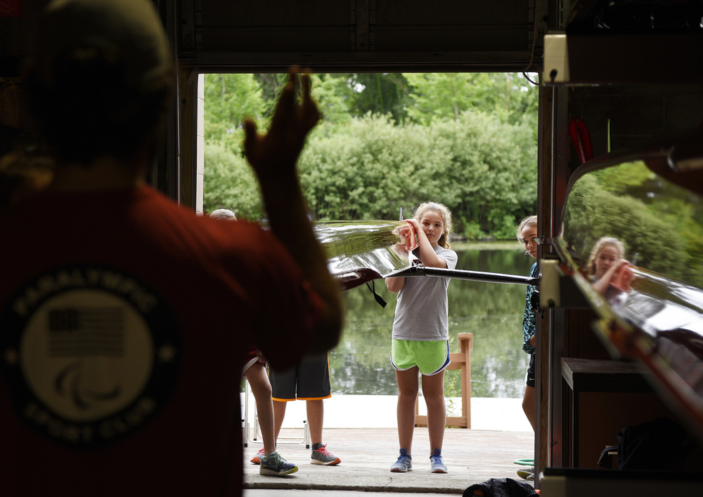 Caitlin Eason, 11, of Winchester helps bring the boat back into the boat house as Grace Preston, 11, of Winchester looks on while instructor Logan Jester of Brighton gives instructions on the first day of the Middle School Learn to Row program at CRI's new Newton location at the Stoller Boat House through a partnership with Lasell College on Monday, July 11, 2016.