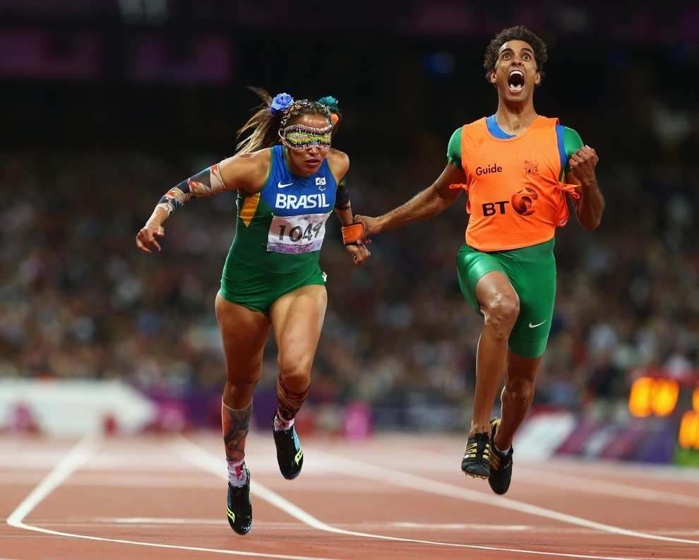 Guide Guilherme Soares de Santana reacts to Terezinha Guilhermina of Brazil winning gold before she knows she's won the Women's 100m T11 Final. [Image by Michael Steele/Getty Images]