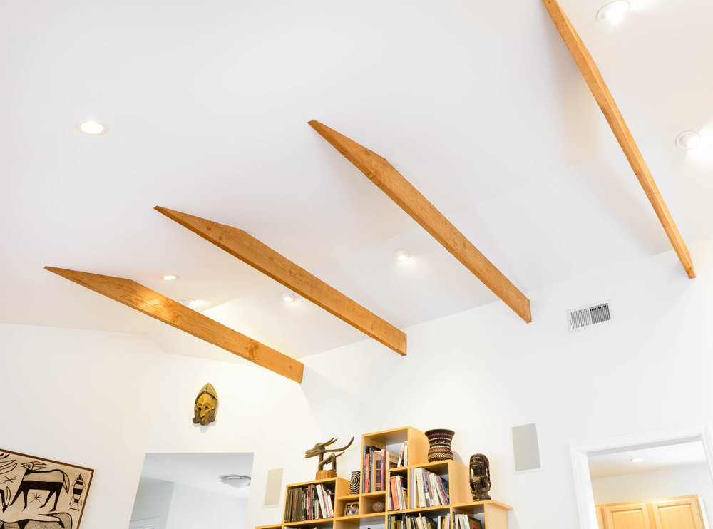 The cathedral ceiling with the exposed structural beams and recessed lighting amplifies the living room's space and light
