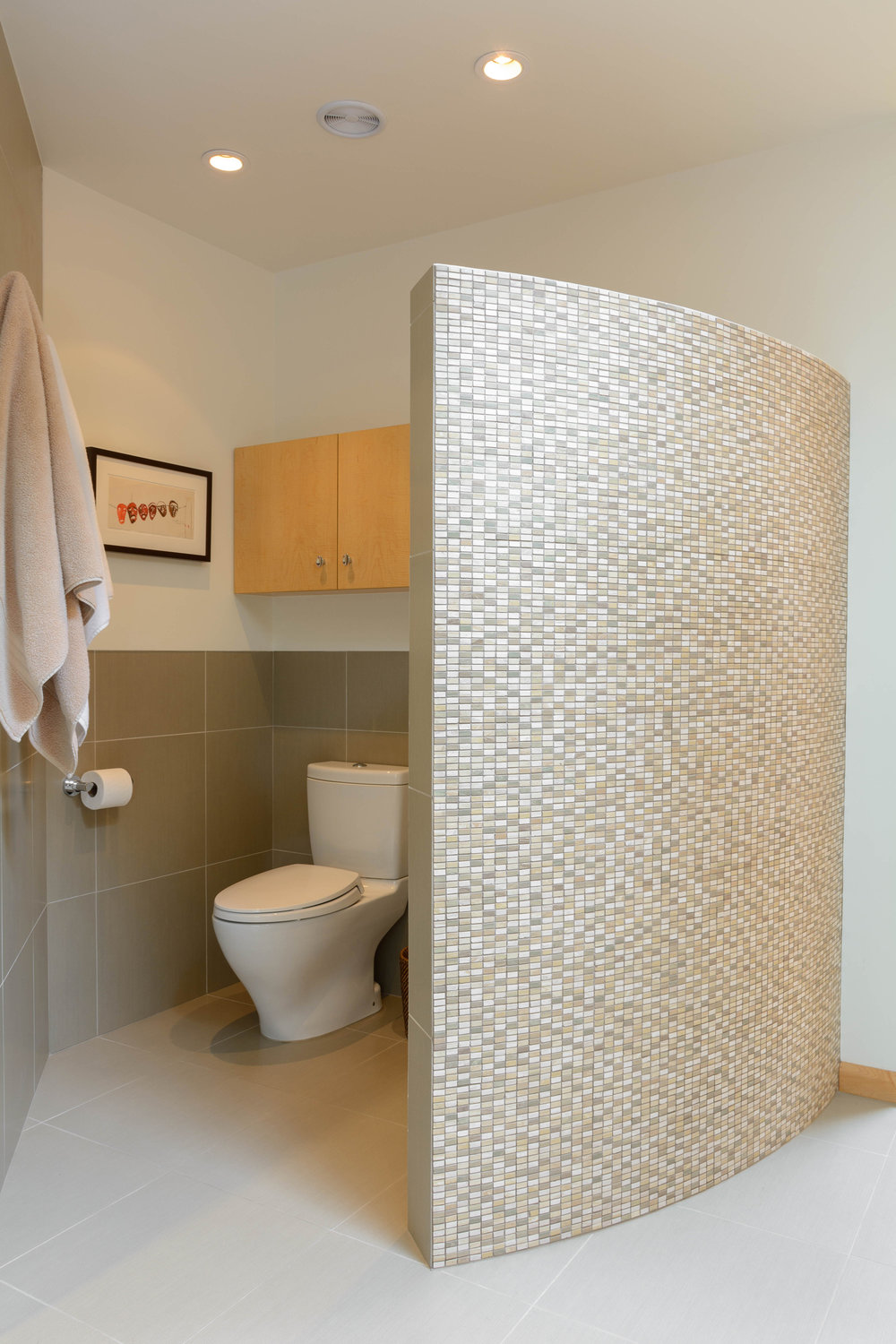 This tiled curved privacy wall separates the water closet and bidet from the rest of the master bathroom