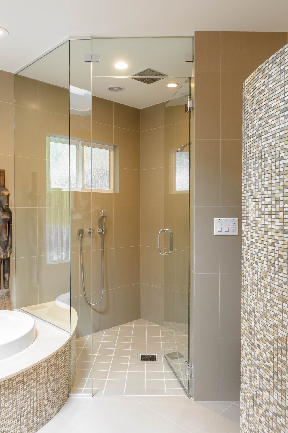 The master bath shower features both rain head and handheld shower fixtures as well as a curbless accessible threshold