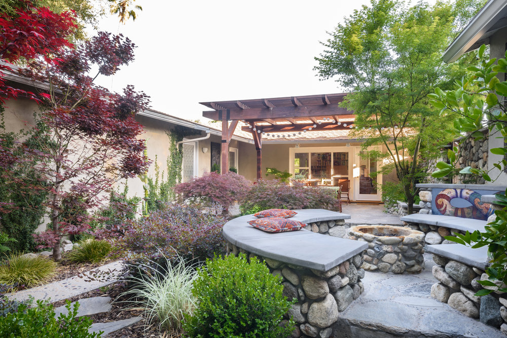 Asian-inspired woodland backyard with a stone fire pit and seating area and a pergola for outdoor dining