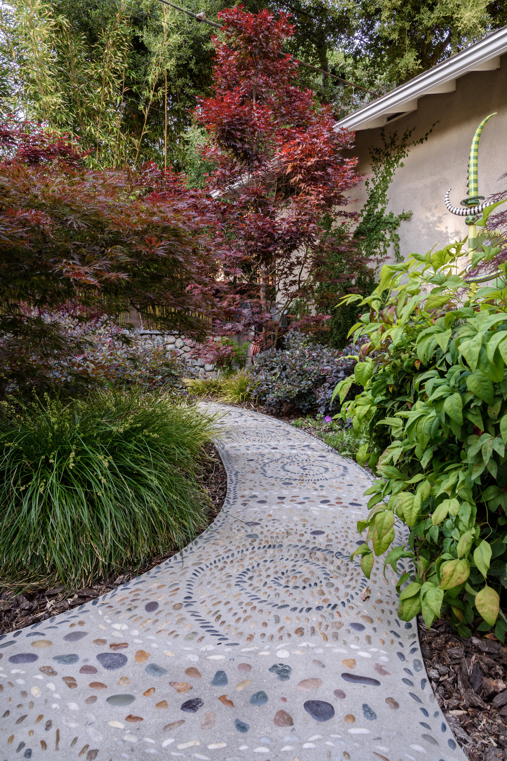 Asian-inspired woodland backyard with bamboo, Japanese maple and mosaic pebble pathways for a peaceful retreat