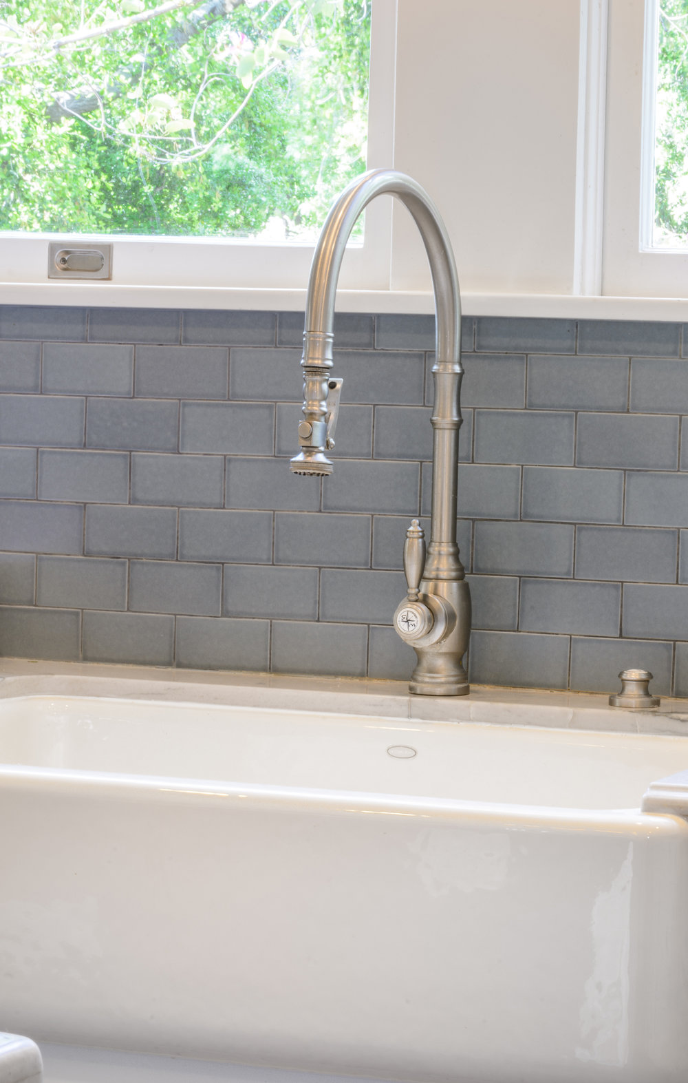 The farmhouse sink, gooseneck faucet, marble counter, light blue tile backsplash and white wood windows enlight simplicity in all its beauty