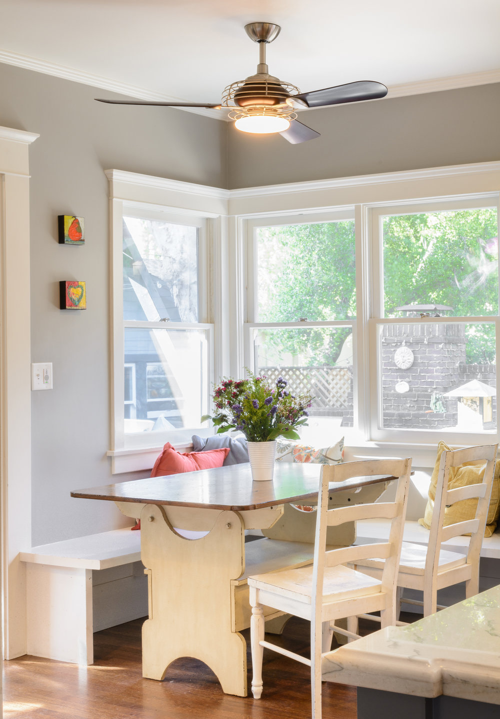 This perfect craftsman style breakfast nook provides a warm welcome thanks to plenty of natural light, white benches, distressed chairs, and a white table base with a wood top