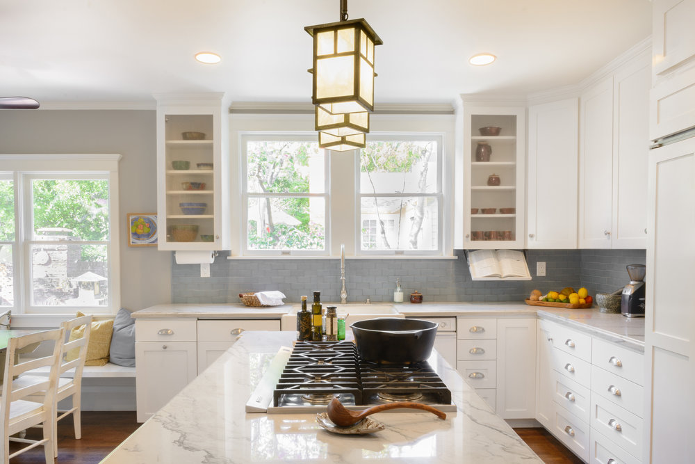 Craftsman style light pendants over island cooktop: a soft accent to this sunlit kitchen with white cabinets