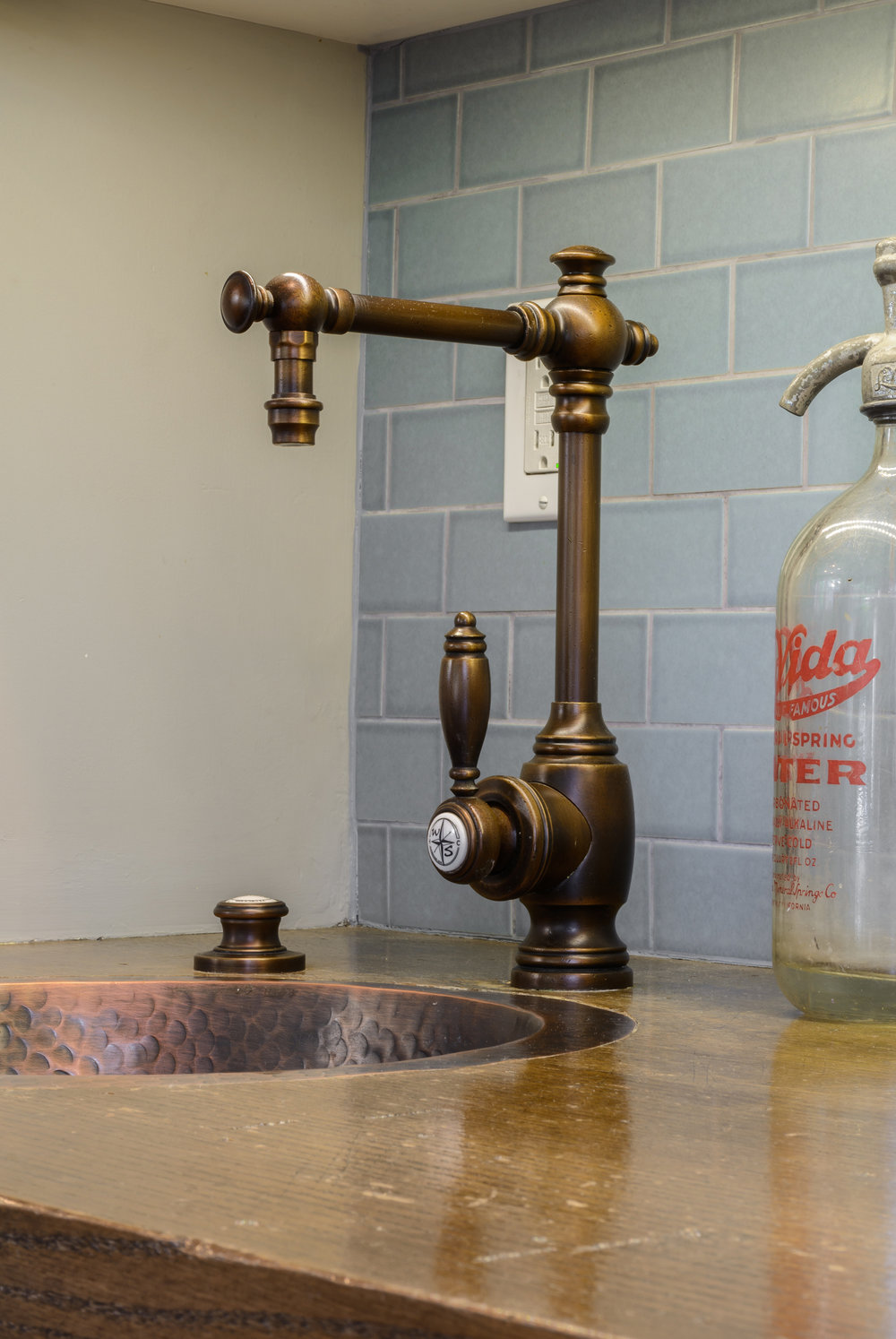Copper bar sink on a wood counter with glass tile backsplash