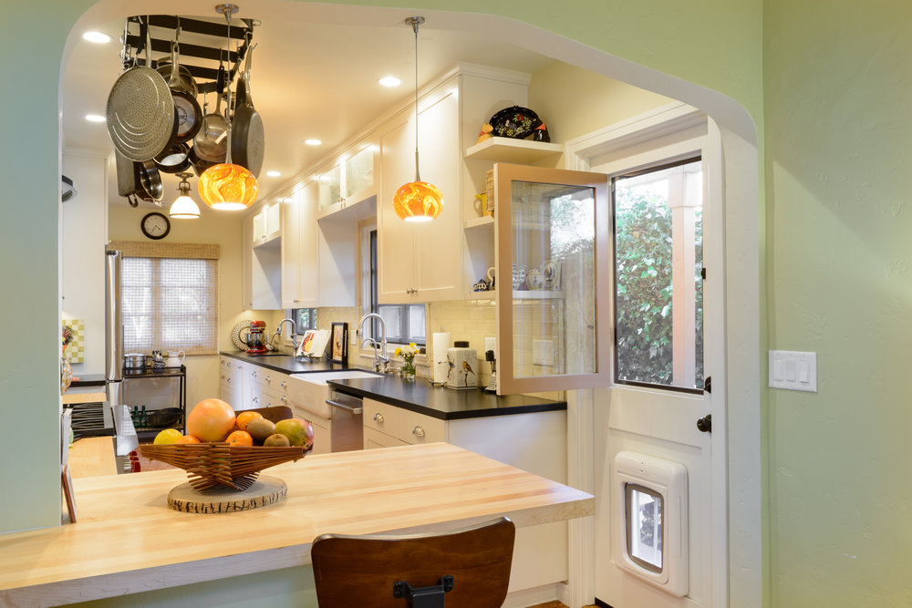The window of this old world style kitchen exterior side door offers a nice breeze for the cooking and bar seating areas