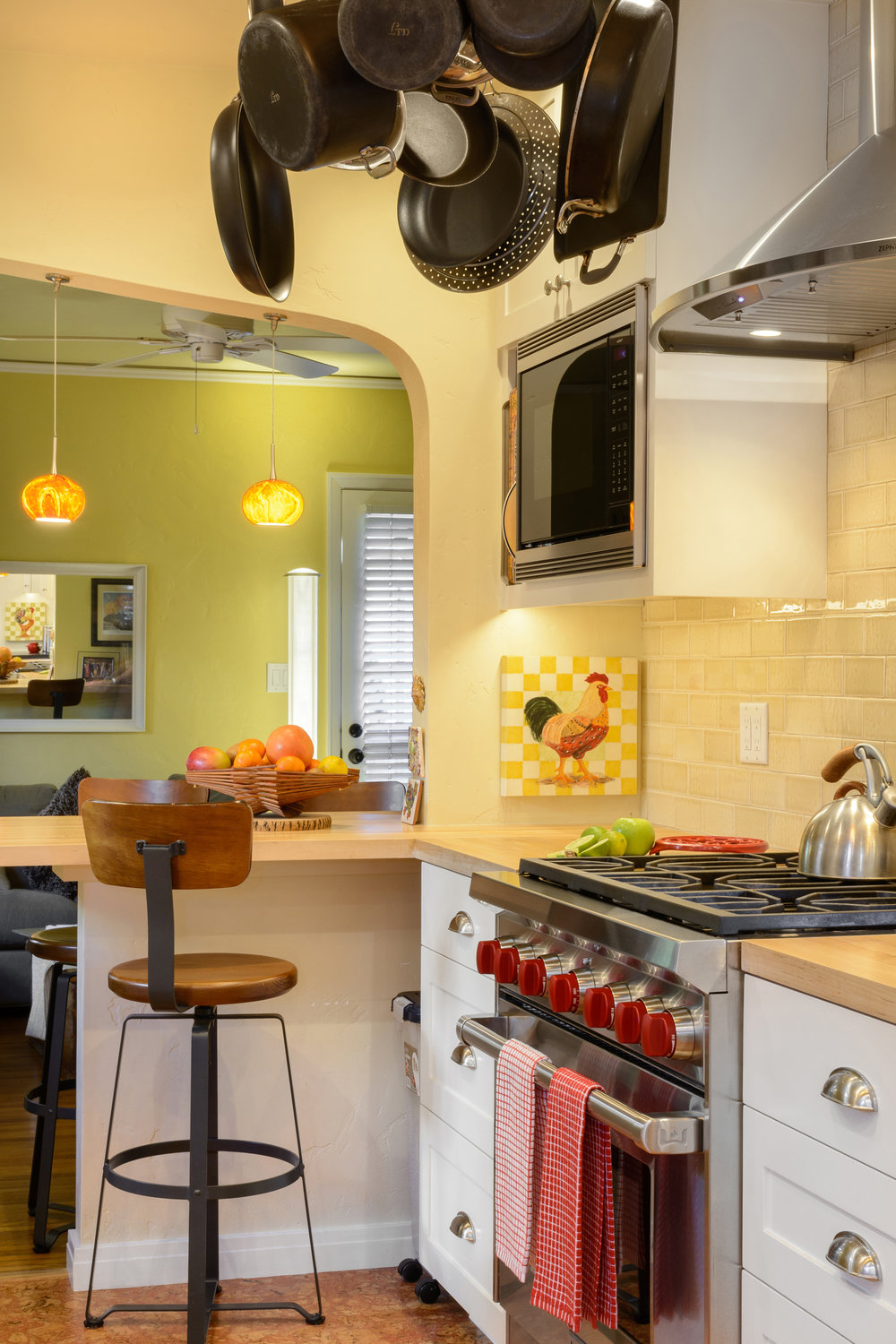 The cooking area of this old world charm kitchen offers a luxurious gas range and hood, a hanging pot rack, a built-in microwave, and white cabinetry with a wood countertop and barstool