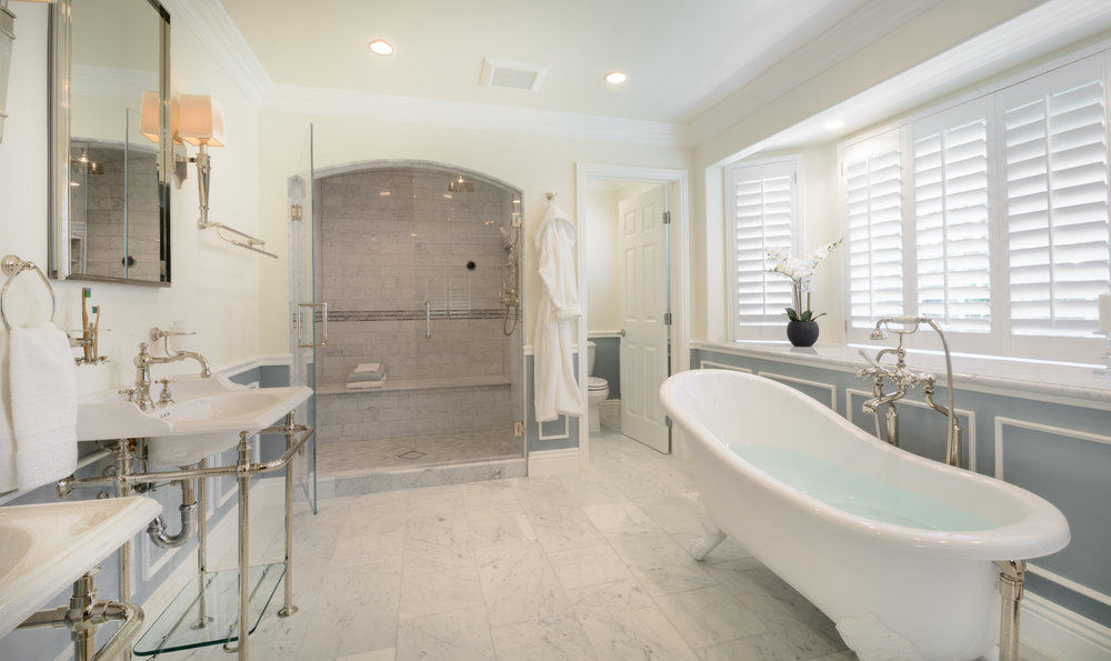 Victorian bathroom: arched carrera shower with carrera marble floor, twin Victoria Albert pedestal sinks, clawfoot bathtub and inspired traditional bathroom fixtures