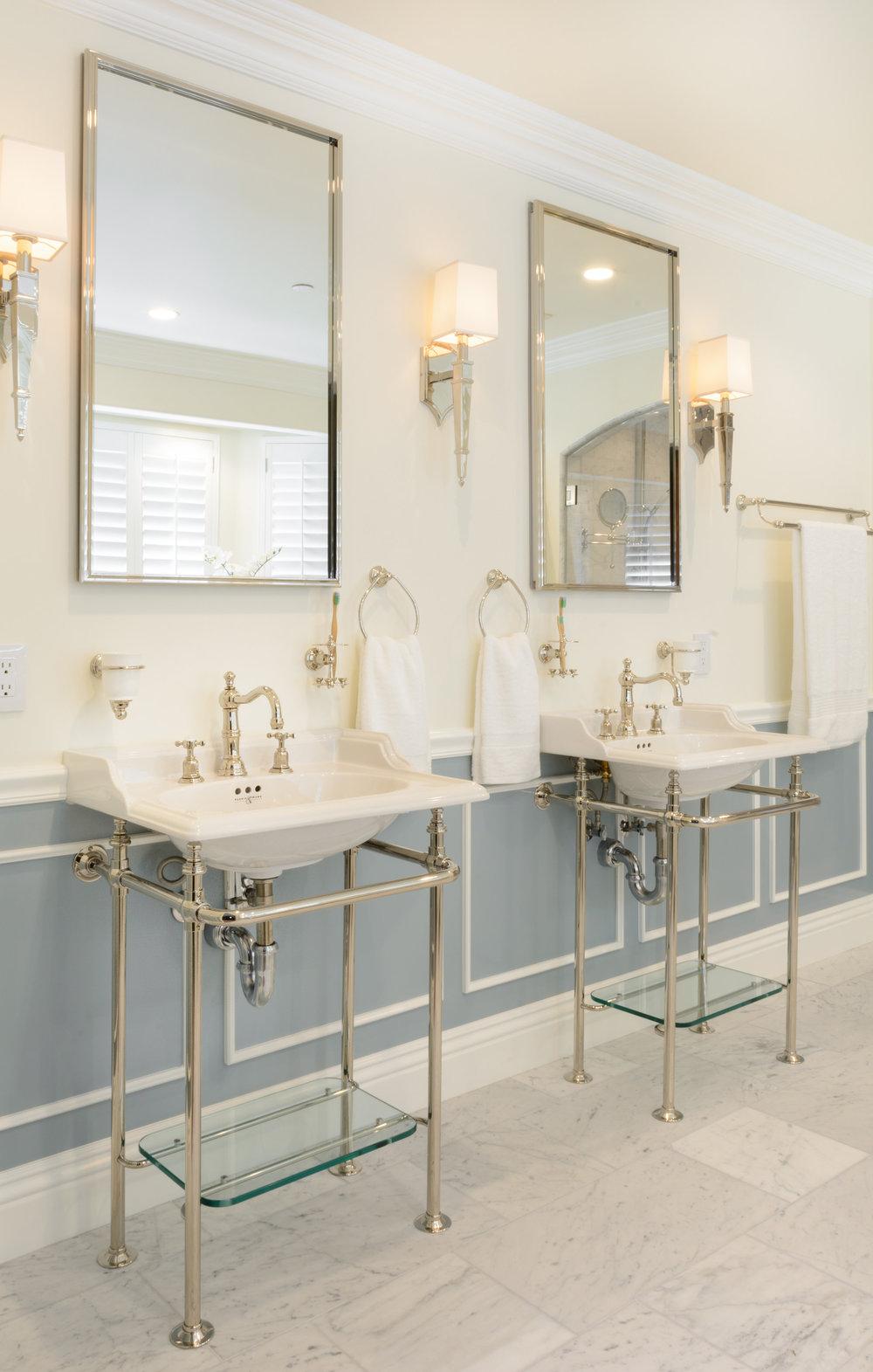 Elegant Victorian design: twin console sinks atop carrera marble floor